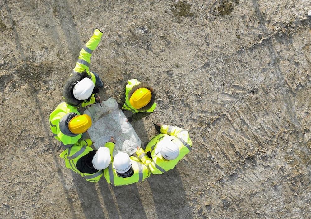 Photo d'un groupe d'ouvrier, communiquant autour d'un plan de chantier, illustrant l'esprit d'équipe au sein de l'entreprise NC Prefa